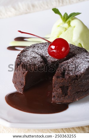 chocolate fondant cake with cherries and mint ice cream on a plate close-up. vertical  - stock photo