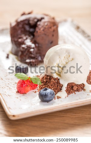 Chocolate fondant lava cake decorated with berries and vanilla ice cream on the table - stock photo