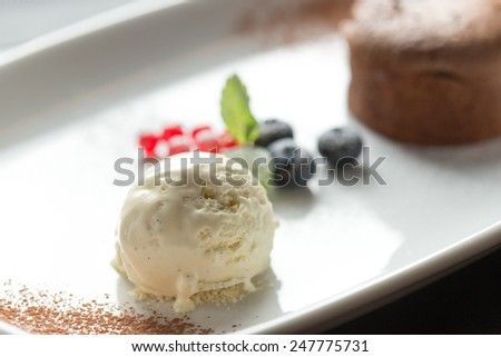 Chocolate fondant lava cake decorated with berries and vanilla ice cream on the table. Close up - stock photo