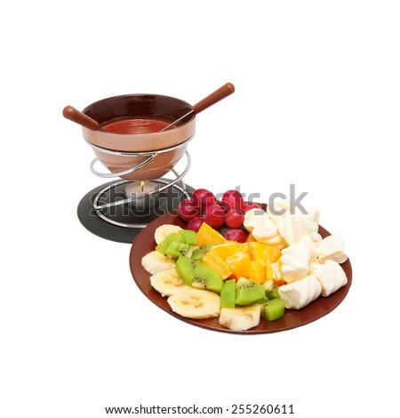 Chocolate fondue and sliced fruits on a plate. Isolated on white background - stock photo