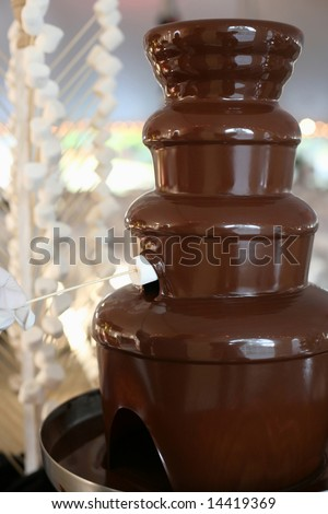 Chocolate fondue fountain with marshmallow being dipped - stock photo