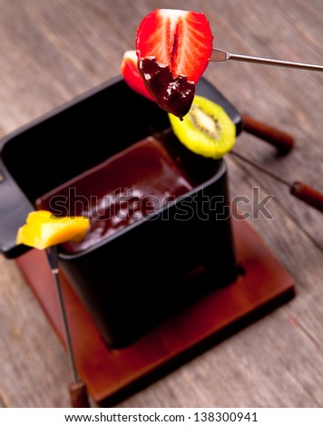 Chocolate fondue with fresh fruits on wood - stock photo