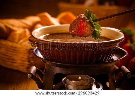 Chocolate fondue with oven on wooden table - stock photo