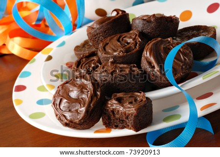 Chocolate frosted brownie bites on festive polka dot plates with colorful ribbons.  Macro with shallow dof. - stock photo