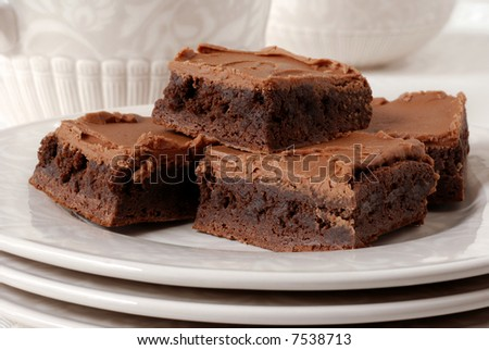 Chocolate frosted brownies on a ceramic plate with matching pitcher and dish in the background.  Shallow dof - stock photo