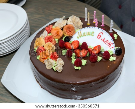 Chocolate fruit cake on plate in birthday with signature on table - stock photo