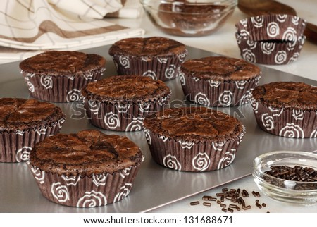 Chocolate fudge brownies - baked individually in fun paper 'brownie cups' on baking sheet-  with bowls of frosting and sprinkles.  Closeup with shallow dof. - stock photo