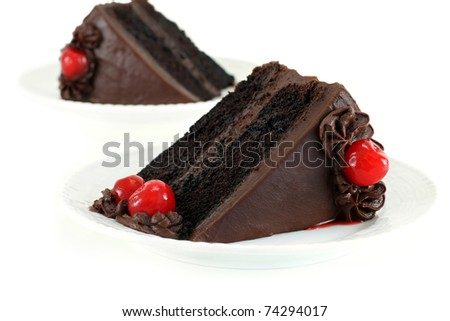 Chocolate Fudge Cake with Chocolate Frosting and Cherries for garnish on a white table.  Selective focus. - stock photo
