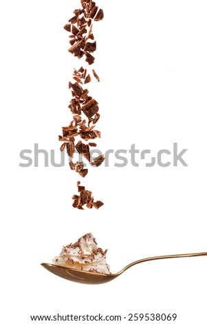 Chocolate glakes falling into a spoon with whipped cream, isolated - stock photo