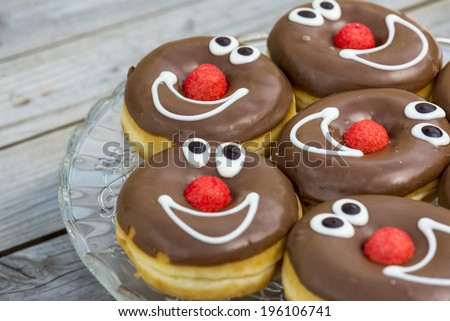 chocolate glazed donuts, with smiling faces. shallow depth of field - stock photo