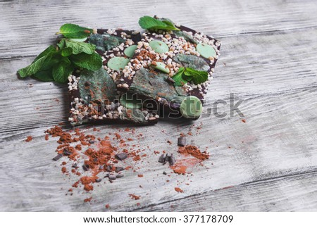 Chocolate, hand-made with mint leaves, candied violets, lemon candy, nuts, chips, cocoa powder on a light wooden background in rustic style - stock photo