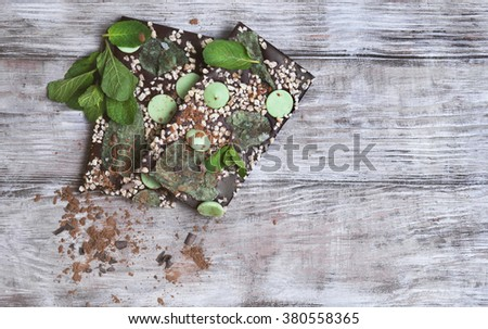 Chocolate, hand-made with mint leaves, candied violets, lemon candy, nuts, chips, cocoa powder on a light wooden background in rustic style, top view, clean empty place for text, for the recipes - stock photo
