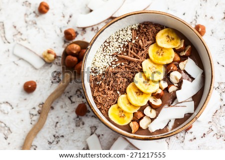 Chocolate hazelnut smoothie bowl topped with sliced banana, shredded coconut, chopped  chocolate, nuts and sesame seeds. - stock photo