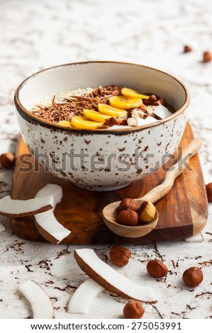 Chocolate hazelnut smoothie bowl topped with sliced banana, shredded coconut, chopped  chocolate, nuts and sesame seeds. Soft focus - stock photo
