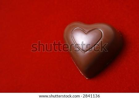Chocolate heart on red velvet background. - stock photo