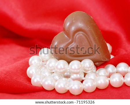 chocolate heart resting on a string of pearls with red satin in the background in a vertical format.  Could be used for Valentine, anniversary or romantic