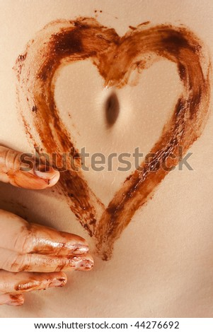 chocolate heart shape on the female belly - stock photo