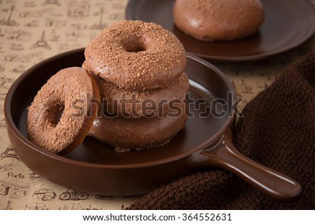 Chocolate homemade donuts on brown newspaper background - stock photo