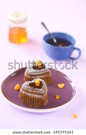 Chocolate Honey and Pecan Heart Cakes with candied orange cubes on a purple plate, a cup of tea and a jar of honey, on a light purple background. - stock photo