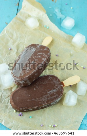 Chocolate ice cream pops on a blue wooden background with ice cubes