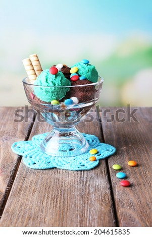 Chocolate ice cream with multicolor candies and wafer rolls in glass bowl, on color wooden table, on bright background - stock photo