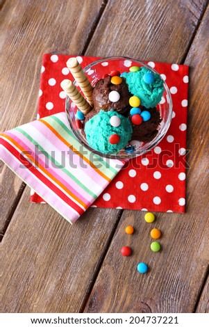 Chocolate ice cream with multicolor candies and wafer rolls in glass bowl, on wooden background - stock photo