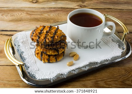 Chocolate icing cookies with peanuts and cup of tea on a metal serving tray with a white lace napkin. Breakfast biscuits and tea. Cookies. Pastry. Biscuits. Homemade cookies. Cookie. Tea. Tea cup    - stock photo