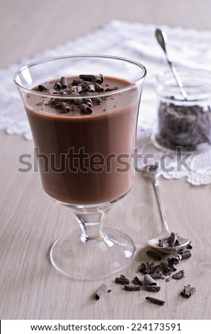 Chocolate jelly in a glass beaker on a wooden surface - stock photo