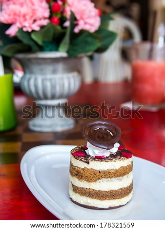 Chocolate  layer cake decorate with chocolate slice on colorful table top - stock photo