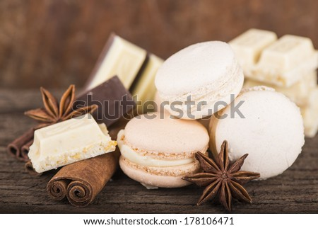 Chocolate macaroons with pieces of white and black chocolate on old wooden table  - stock photo