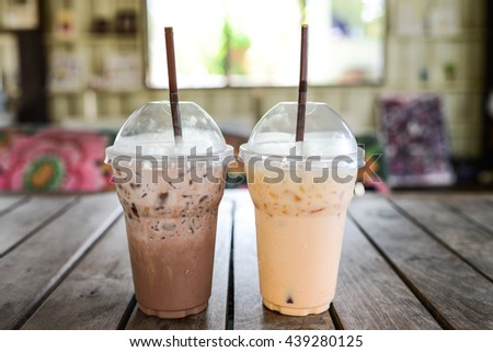 chocolate milk and ice milk tea in take away plastic cup on vintage Background - stock photo
