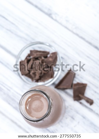 Chocolate Milk in a small bottle (on bright wooden background) - stock photo