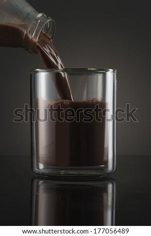 Chocolate Milk Pouring into glass - stock photo