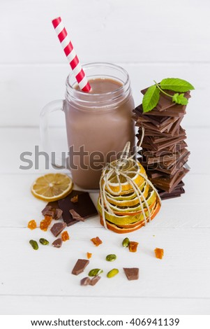 Chocolate milk with chocolate on white wooden table. - stock photo