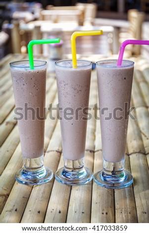 Chocolate milkshakes on bamboo table - stock photo