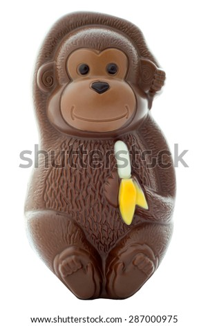 Chocolate monkey figurine holding a banana on an isolated white background with a clipping path - stock photo