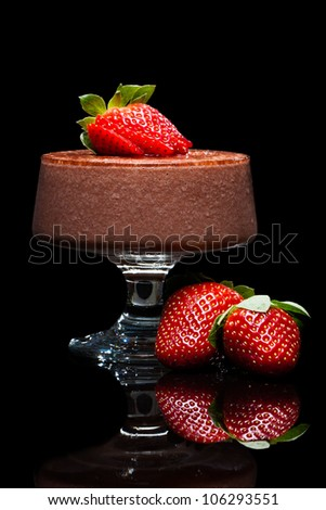 Chocolate mousse dessert with delicious red strawberries. Isolated on black. - stock photo