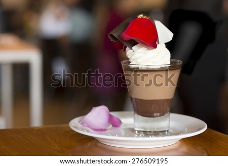 Chocolate Mousse in Glass Cup Decorated with Rose Petals - stock photo