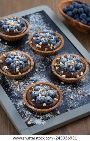 chocolate mousse with blueberries and nuts in tartlets, vertical, top view - stock photo