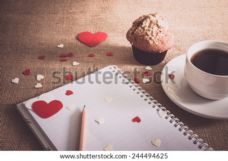 chocolate muffin and coffee and red and white hearts, notebook, pencil on sackcloth textures