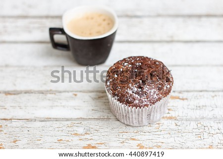 chocolate muffin and cup of coffee on the white wooden background - stock photo