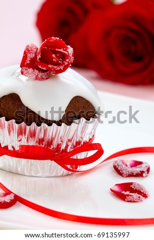 Chocolate muffin garnished with sugar frosted rose and vanilla icing. Valentine's day or wedding desert. - stock photo