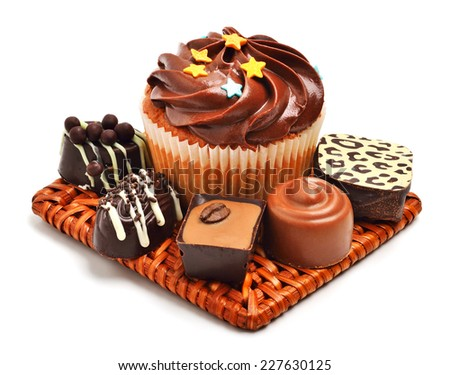 Chocolate muffin with chocolate sweets, candies isolated on white background - stock photo