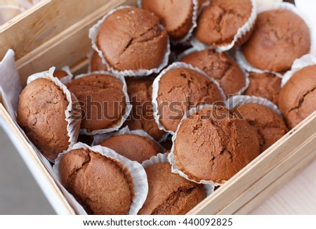 Chocolate muffins closeup in wooden tray. Plenty of chocolate cocoa muffins fresh baked for sale at country fair. Sweet food, snacks, desserts background. Bakery products - stock photo
