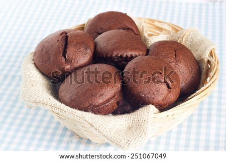 Chocolate muffins in a straw basket placed on blue checkered table cloth. - stock photo
