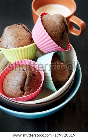 Chocolate Muffins in Colorful Silicone Forms and Cup of Milk , Sweet Dessert - stock photo