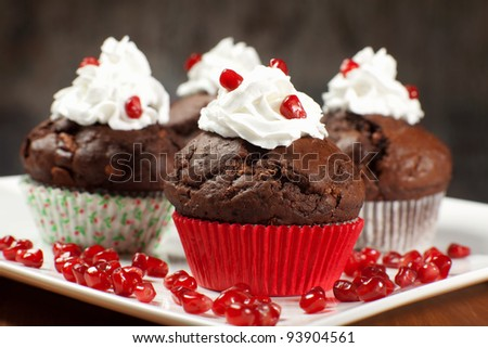chocolate muffins with cream and pomegranates - stock photo