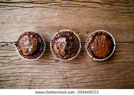 Chocolate muffins with crispy top on Wood Table Background, Rustic Still Life Style / Concept and Idea of Sweet Food Bakery Dessert Time, To Eat with Coffee or Hot Drink in the Morning or Tea Time. - stock photo