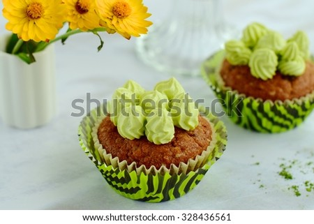 Chocolate muffins with Matcha cream cheese frosting - stock photo