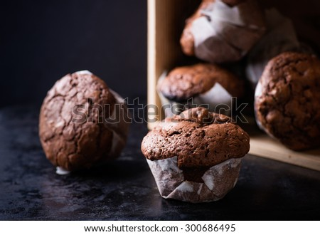 Chocolate muffins with nuts on dark background, selective focus - stock photo
